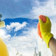 Spring cleaning - someones hands in yellow gloves with spray and ruber cleaning window, spring bright blue sky in background
